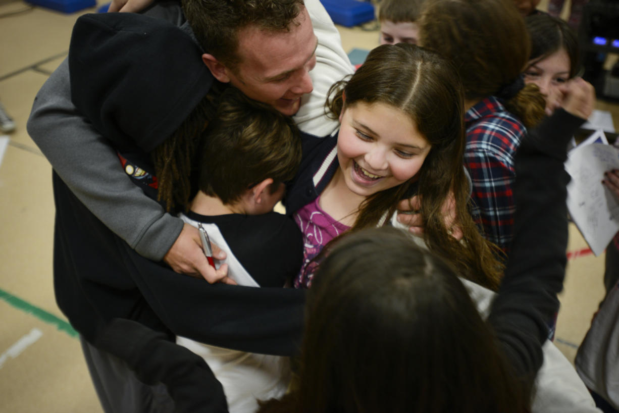 Fifth-grader Alicia Zuniga participates in a group hug with professional endurance athlete Colin O'Brady at Hearthwood Elementary on Wednesday. O'Brady summited the tallest mountain in each of the seven continents and skied to the North and South poles. His next goal: raising $1 million to inspire active, healthy kids with his foundation, Beyond 7/2. (Ariane Kunze/The Columbian)