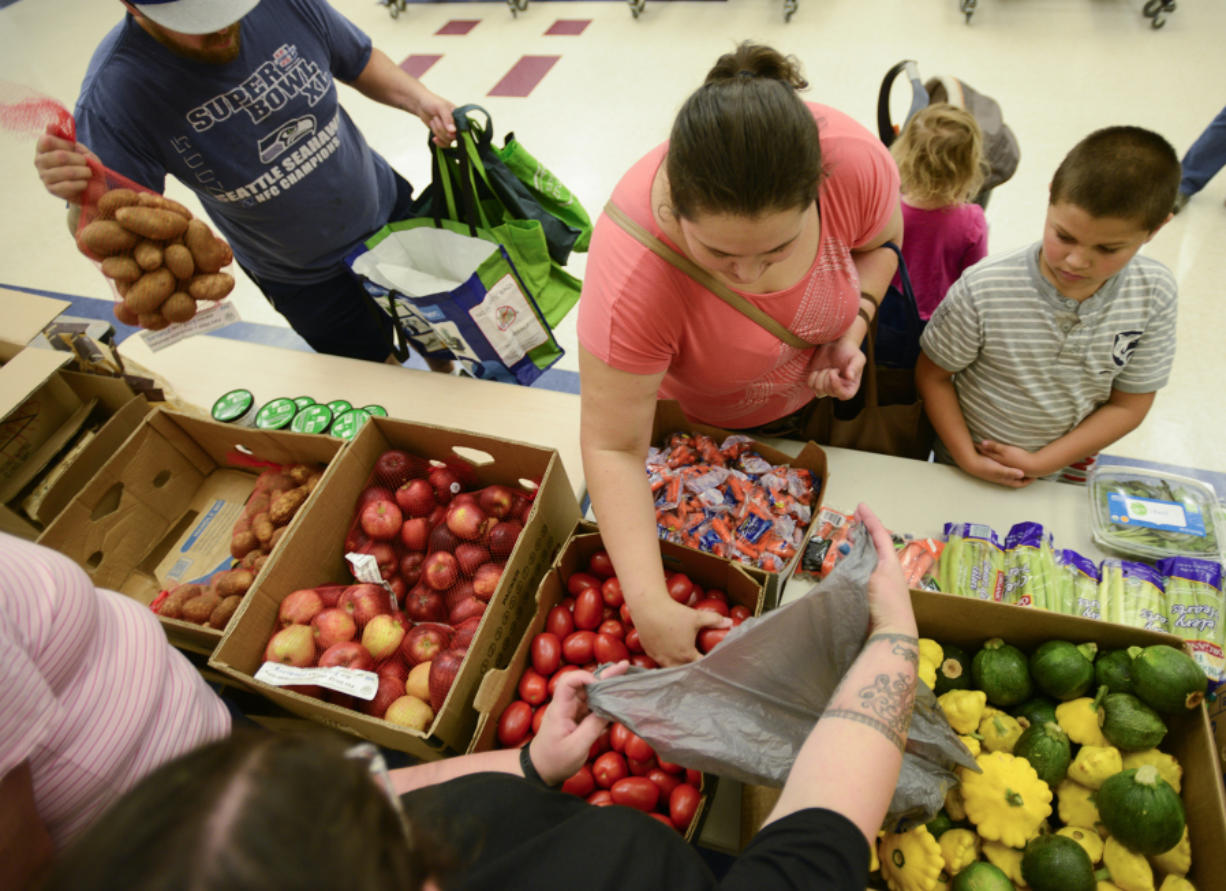 Nataliya Romashcheko, center, selects tomatoes with her son, Misha Romashcheko, 8, right, at the fresh food pantry at Orchards Elementary School on Wednesday.