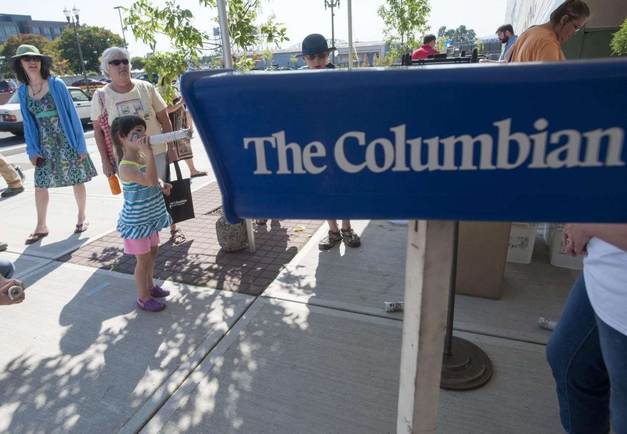 Bailey Rose played a game of throwing a paper in to a plastic receptacle at an event at The Columbian in Vancouver on Sept. 12. The event was held in advance of The Columbian newspaper's 125th anniversary in October. The Columbian announced layoffs on Wednesday.