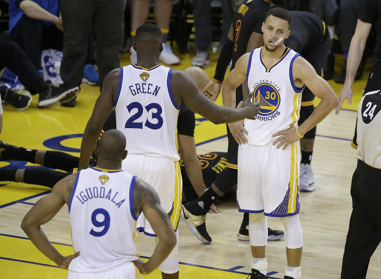 Golden State Warriors guard Stephen Curry (30), forward LeBron James (23) and forward Andre Iguodala (9) stand on the court as Cleveland Cavaliers forward LeBron James, on ground, is tended to during the second half of Game 7 of basketball's NBA Finals in Oakland, Calif., Sunday, June 19, 2016. The Cavaliers won 93-89.