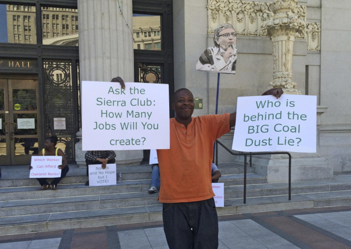 Stevie Johnson holds up a pair of signs during a protest outside City Hall before a scheduled vote, Monday, June 27, 2016, to decide whether to ban rail shipments of coal over concerns it would pose a public health or safety hazard in Oakland, Calif. A yes vote Monday by the Oakland City Council could scuttle the plan to build a marine terminal that would serve as a gateway for Utah coal heading to Asia.