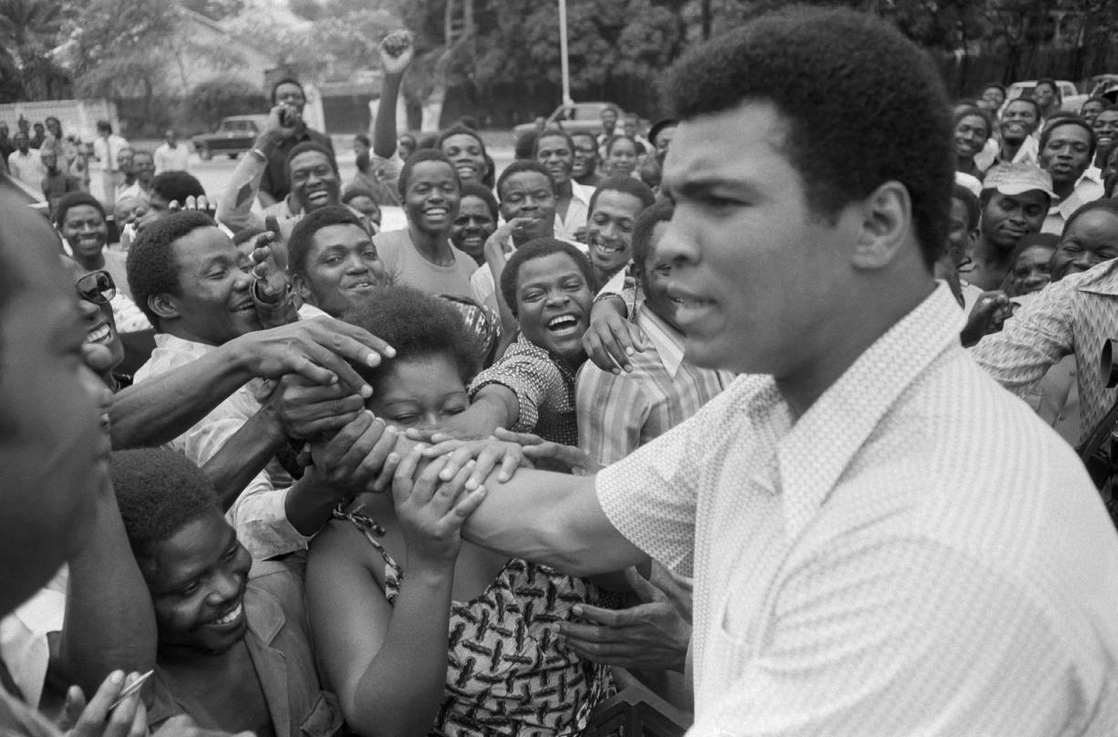 Muhammad Ali is greeted in downtown Kinshasa, Zaire, on Sept. 17, 1974. Ali was in Zaire to fight George Foreman. Ali, the magnificent heavyweight champion whose fast fists and irrepressible personality transcended sports and captivated the world, died on Friday, June 3, 2016. He was 74.
