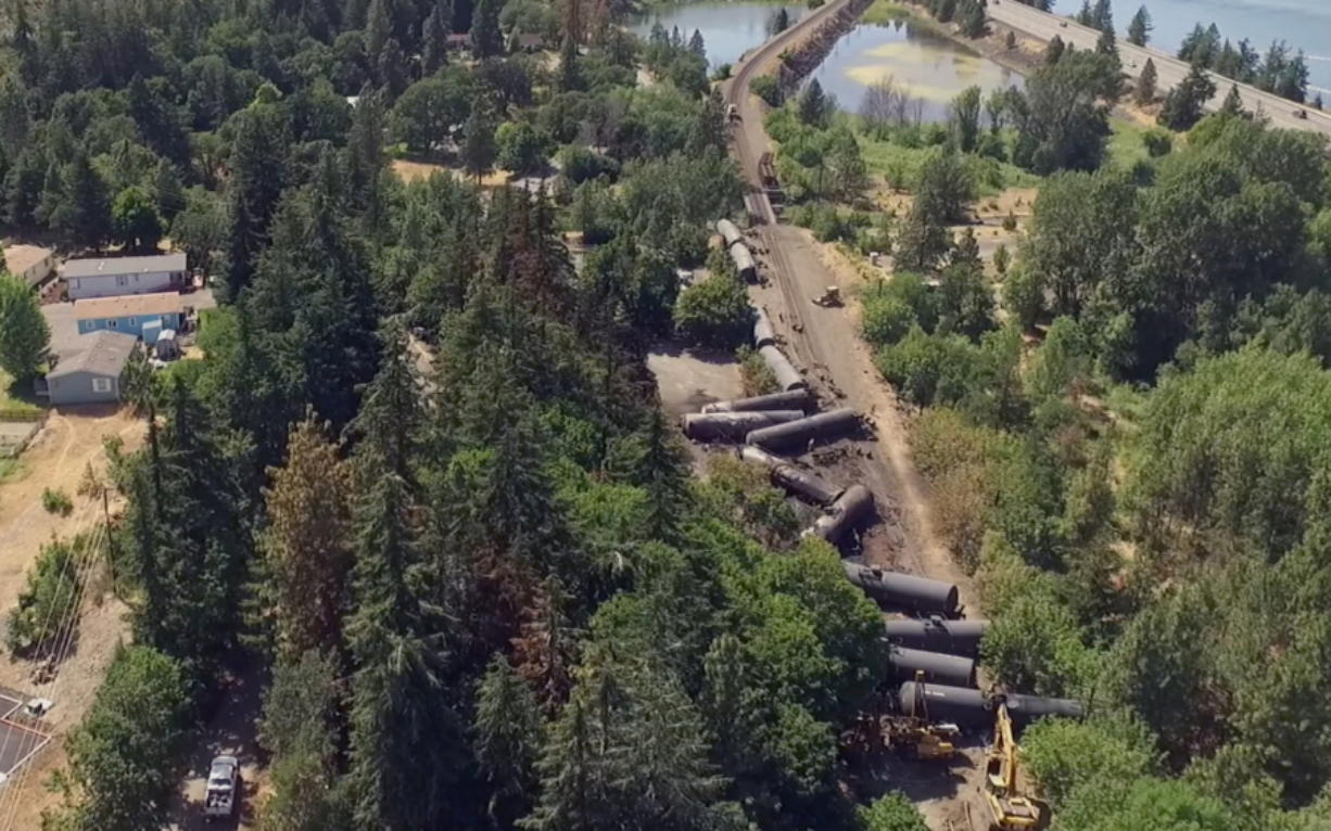 This video image taken from a drone shows an aerial view of crumpled oil tankers lying beside the railroad tracks after a fiery train derailment on June 3 prompted evacuations from the tiny Columbia River Gorge town about 70 miles east of Portland on June 6  in Mosier, Ore. The Union Pacific train derailment comes as a massive oil-storage terminal proposed along the Columbia River in southwest Washington is under review. (Brent Foster via AP)
