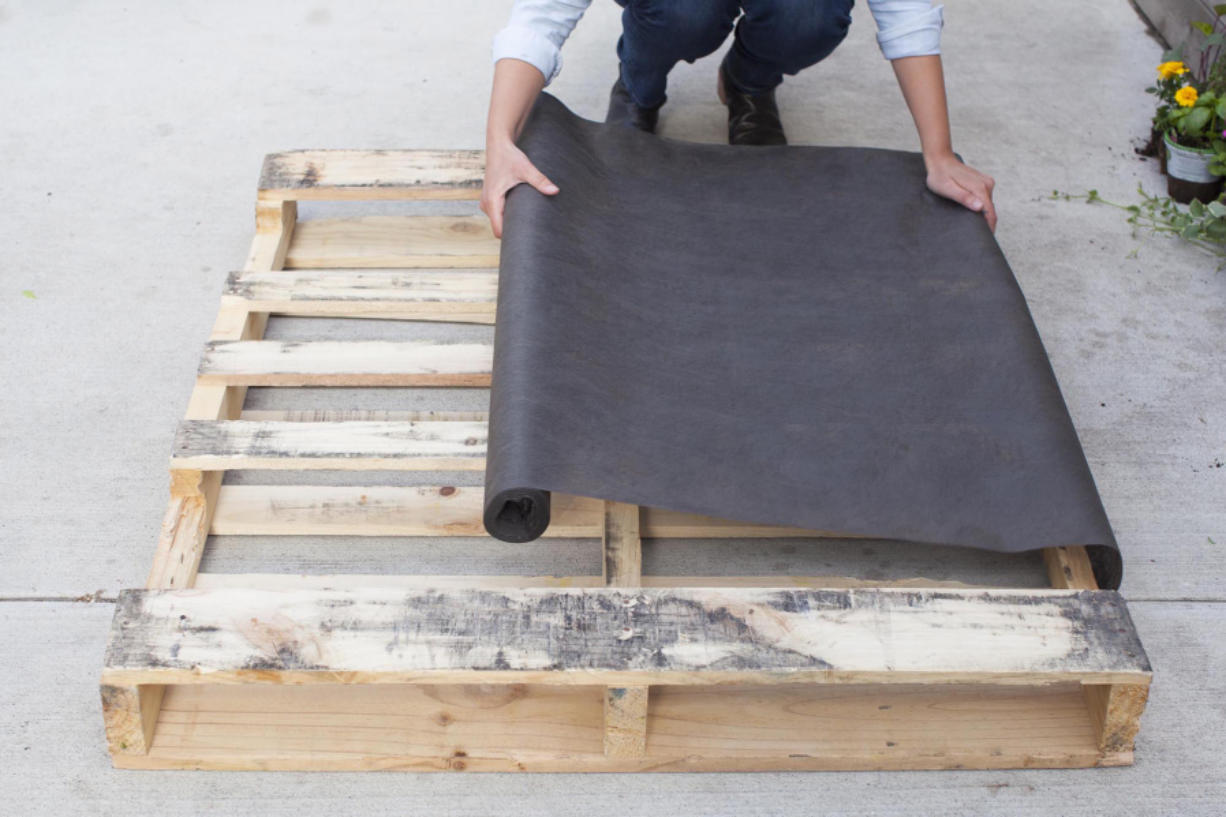 Lay your pallet flat, with the side you want facing front on the ground; it should have several horizontal planks. Cut landscaping fabric to cover the back and sides of the pallet.