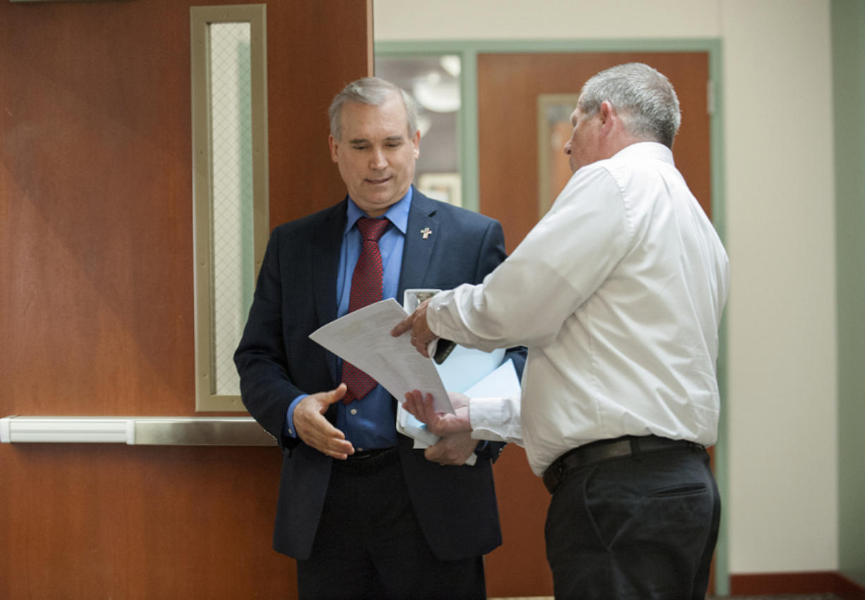 Clark County Councilor David Madore, left, is served with a summons by process server Brian Davis Tuesday morning at the Clark County Public Service Center.