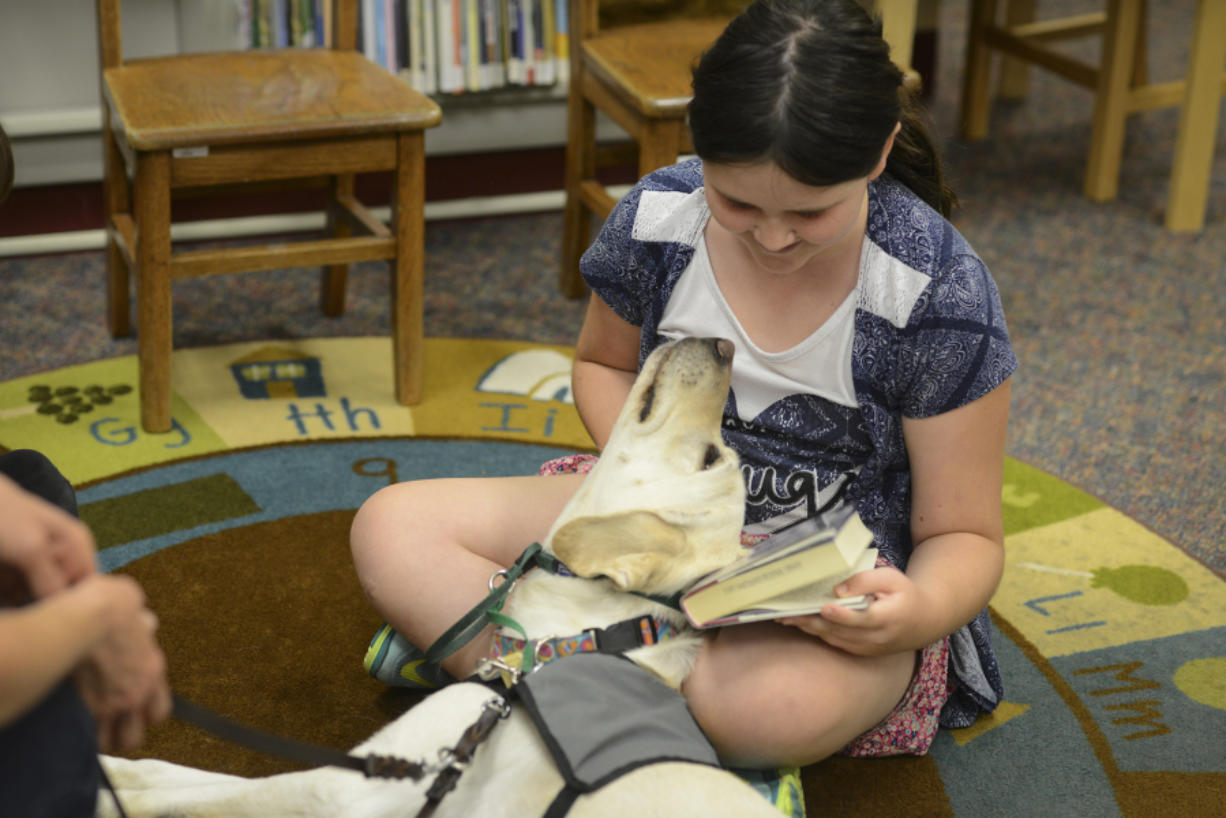 """Limon snuggles up as Cora McGill, 9, reads """"The Time of the Fireflies"""" to her as part of the Ridgefield Community Library's Read to the Dogs program through the Portland Area Canine Therapy Teams program."""