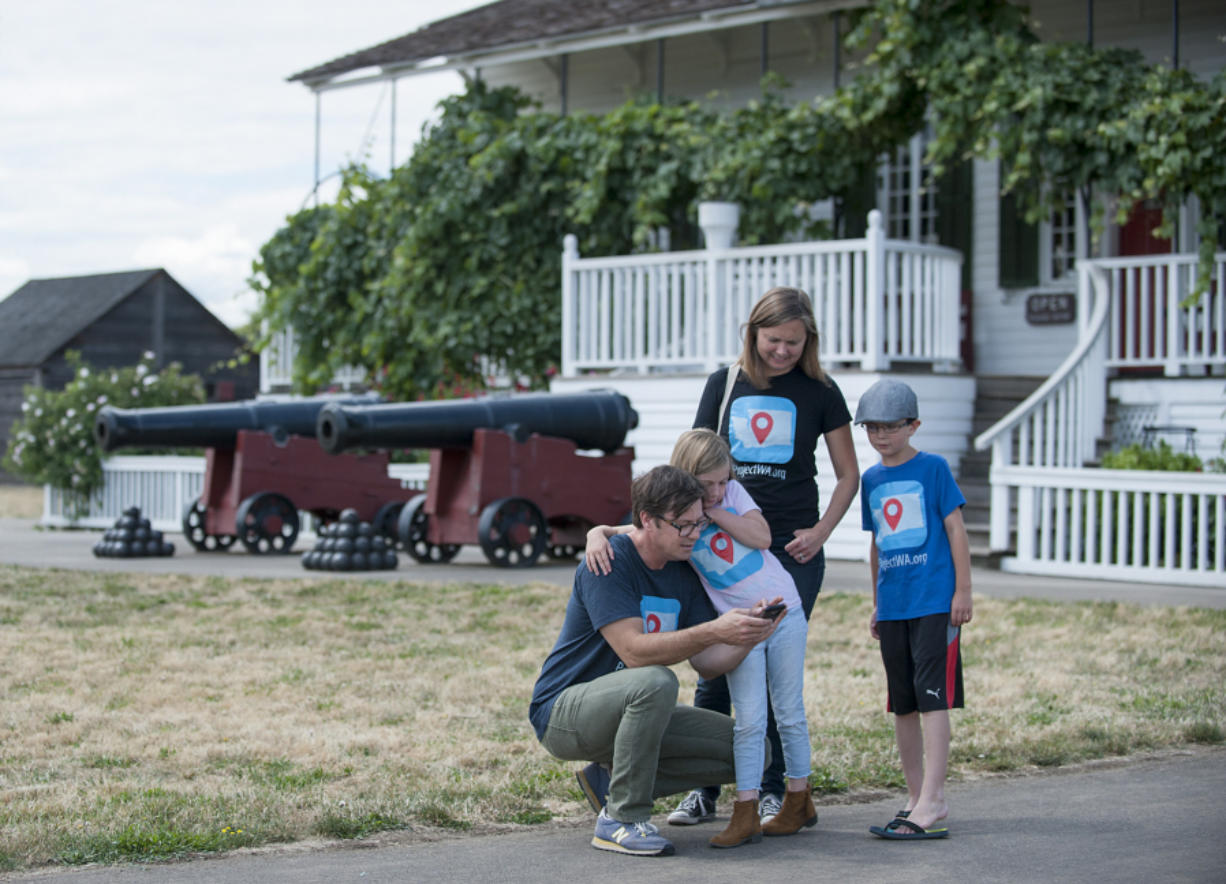 Tim Fry, from left, shows daughter Ruby, wife Kristine and son Henry information about Fort Vancouver on his smartphone app. The family from Lopez Island is touring state historical sites after Tim Fry helped eighth-grade students develop the app.