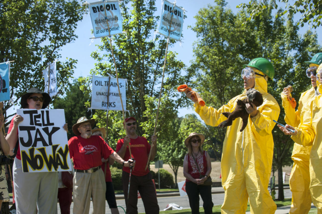 Tara Herberger wore a hazmat suit and carried an oil-stained wolf stuffed animal during a protest over the proposed oil terminal on the final day of adjudication hearings Friday at Clark College Technical Center. With the trial-like hearings concluded, the Energy Facility Site Evaluation Council will issue a recommendation to the governor, possibly later this year, whether to approve or deny the Vancouver Energy terminal project.