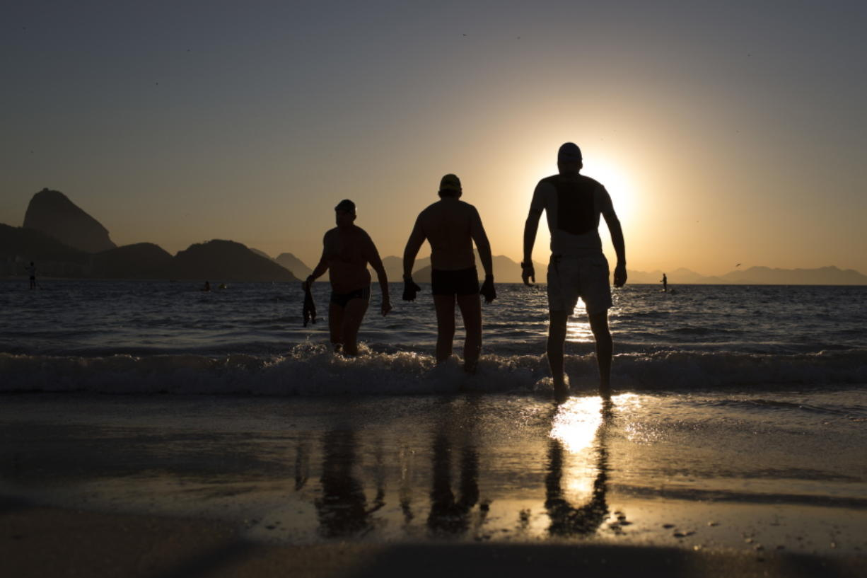 People enter the water for a morning swim at Copabacana beach in Rio de Janeiro, the starting point for the road cycling, marathon swimming and triathlon competitions.