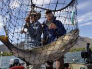 Salmon fishing guide Dave Grove, left, nets a fall chinook for David Moershel while fishing on the Columbia River in Eastern Washington.