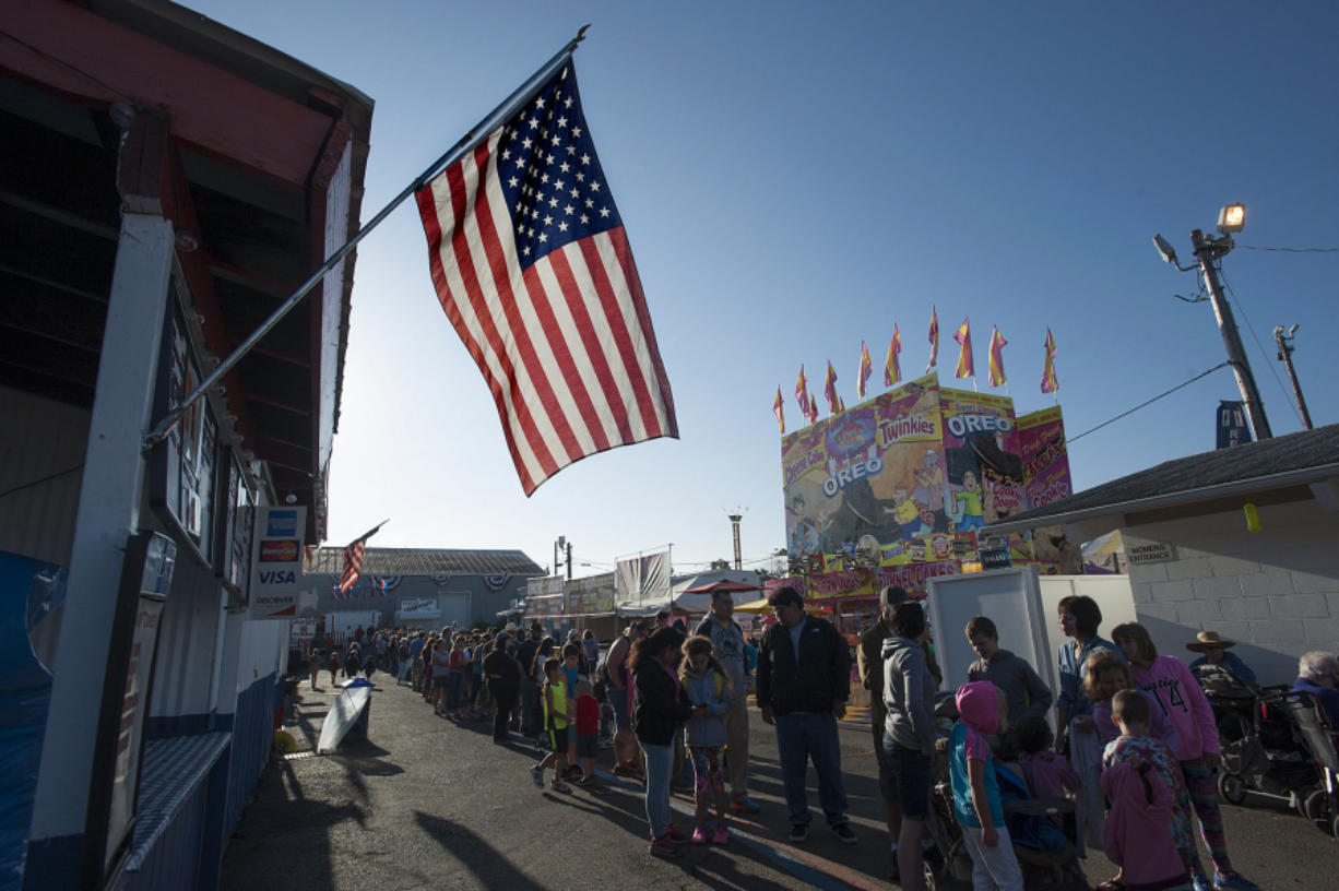 An American flag flies overhead as a long line of people wait for their pancake breakfast Friday morning, the opening day of the 2016 Clark County Fair.