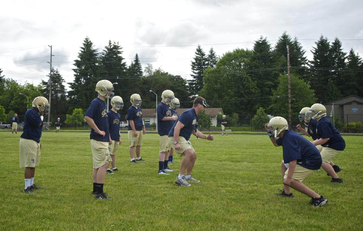 Seton Catholic High School offensive line coach Kasey Powers, center, puts players through a drill during football practice at Cascade Middel School on Thursday May 31, 2012.