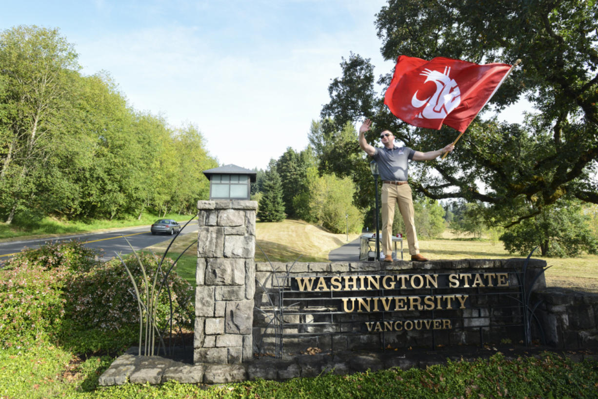 Alumnus Max Ault stands atop the Washington State University Vancouver sign, waving a banner to welcome students to the first day of fall classes. Ault said he fondly remembers his time at WSU Vancouver.
