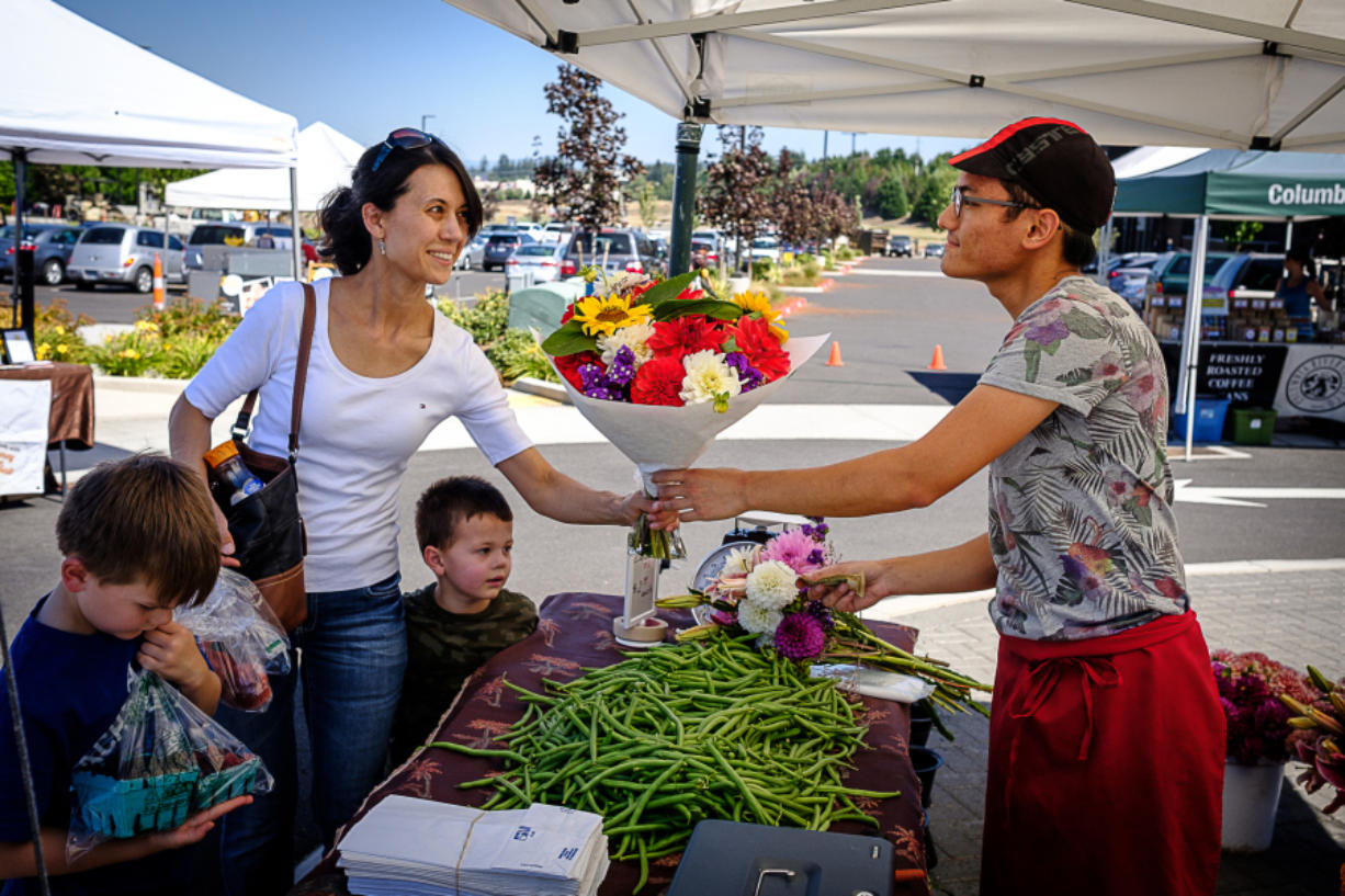 Jacky Yang of Yang's Fresh Bloomer and Produce hands a bouquet of flowers to Pamela Roberts at the farmers market in east Vancouver Aug. 4. The market is in its second year as the Columbia Tech Center looks to build a sense of community on the east side of the city.