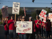 Teacher librarians Kristie Peak of Mill Plain Elementary School, foreground, and Beth Pfenning of Hearthwood Elementary School join picketers Friday morning, Aug. 19, 2016 in Southeast Vancouver.