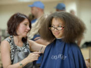 Lisa Houser, left, owner of Utopia Salon, cuts the hair of Arieanna Howard, 11, at the Go Ready back-to-school event Friday at Hudson's Bay High School. Arieanna will be in 6th grade at Discovery Middle School.