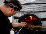 Joey Chmiko, owner and chef of Nonavo Pizza, adds wood to the oven at his newly opened pizzeria in downtown Vancouver on Wednesday. Despite a quiet opening, Nonavo is already selling out of lunch and dinner on occasion.