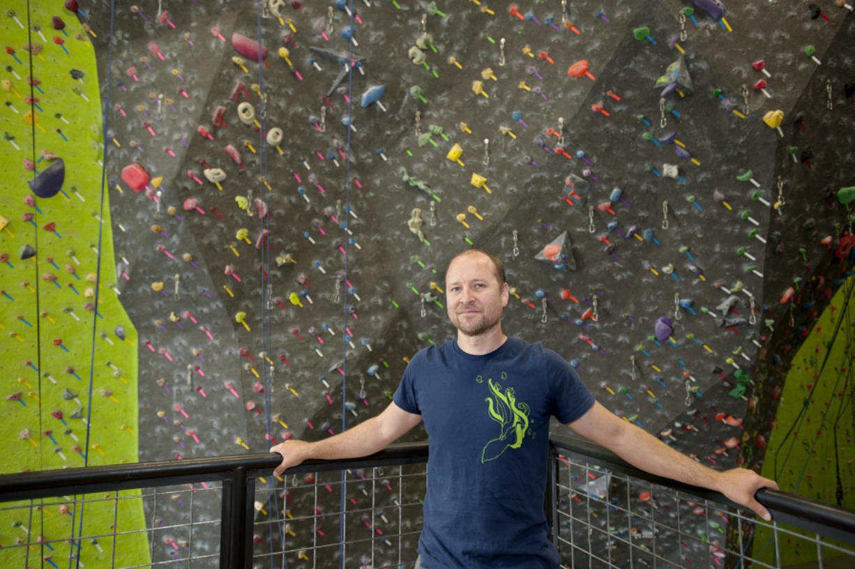 Hanz Kroesen, co-owner of Source Climbing Center, prepares routes for climbers.