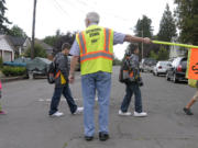 Children walk on their way to the first day of classes at Washington Elementary School in 2014 with help from Mick Hawthorn and other walking school bus volunteers.