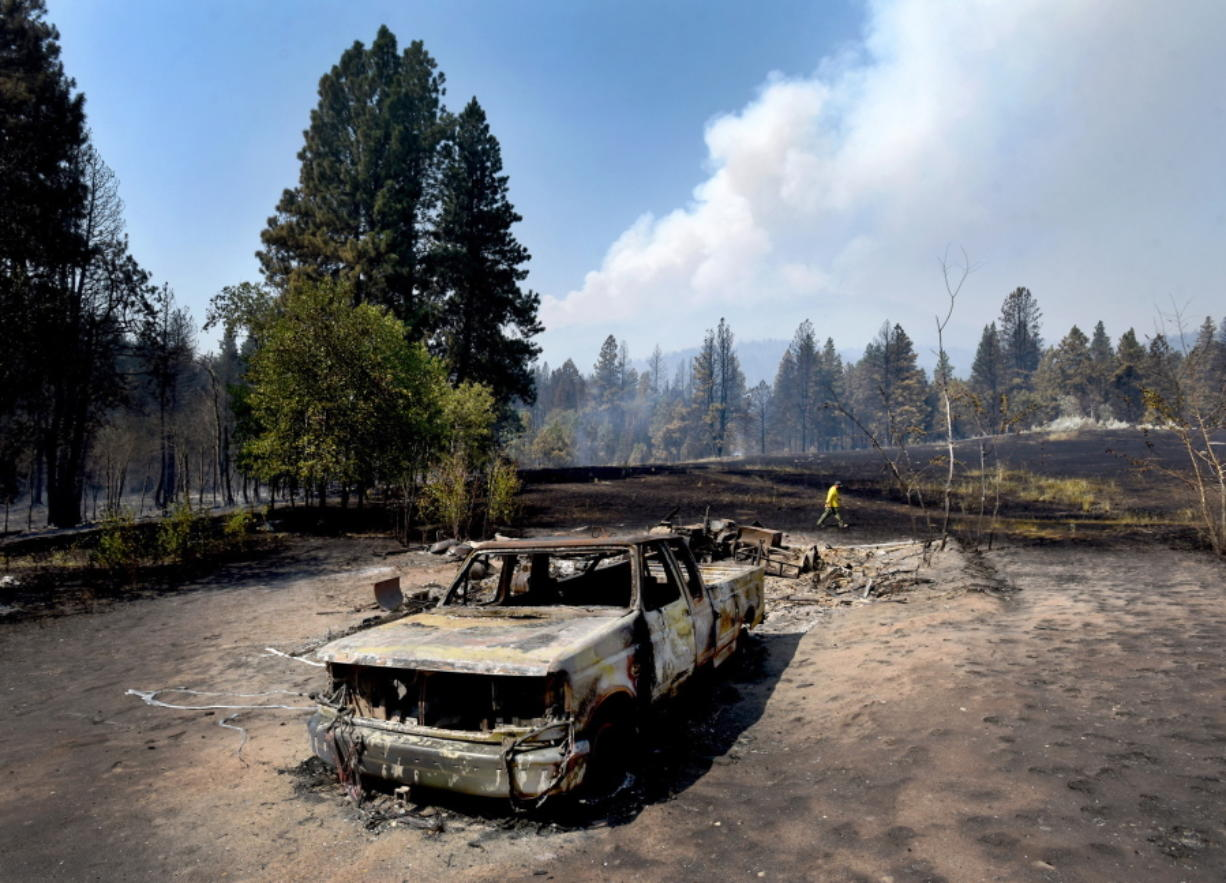Tod McKay, spokesman for the Bitterroot National Forest, at rear, walks past a burned truck and shop at Dave Campbell's home in Hamilton, Mont. Campbell's house survived.