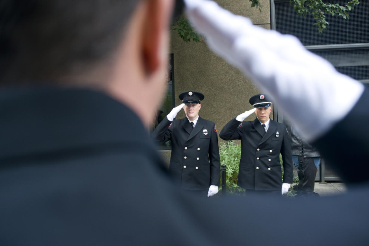 Captain Tyler Dillmon, left, and Marc Patchin, are framed by fellow Vancouver fireman Joe Hudson in salute during the Patriot Day ceremony at Vancouver City Hall on Sunday, Sept. 11, 2016. The ceremony was held in remembrance of the nearly 3,000 people who died in the terrorist attacks on September 11, 2001. (Samuel Wilson for the Columbian)