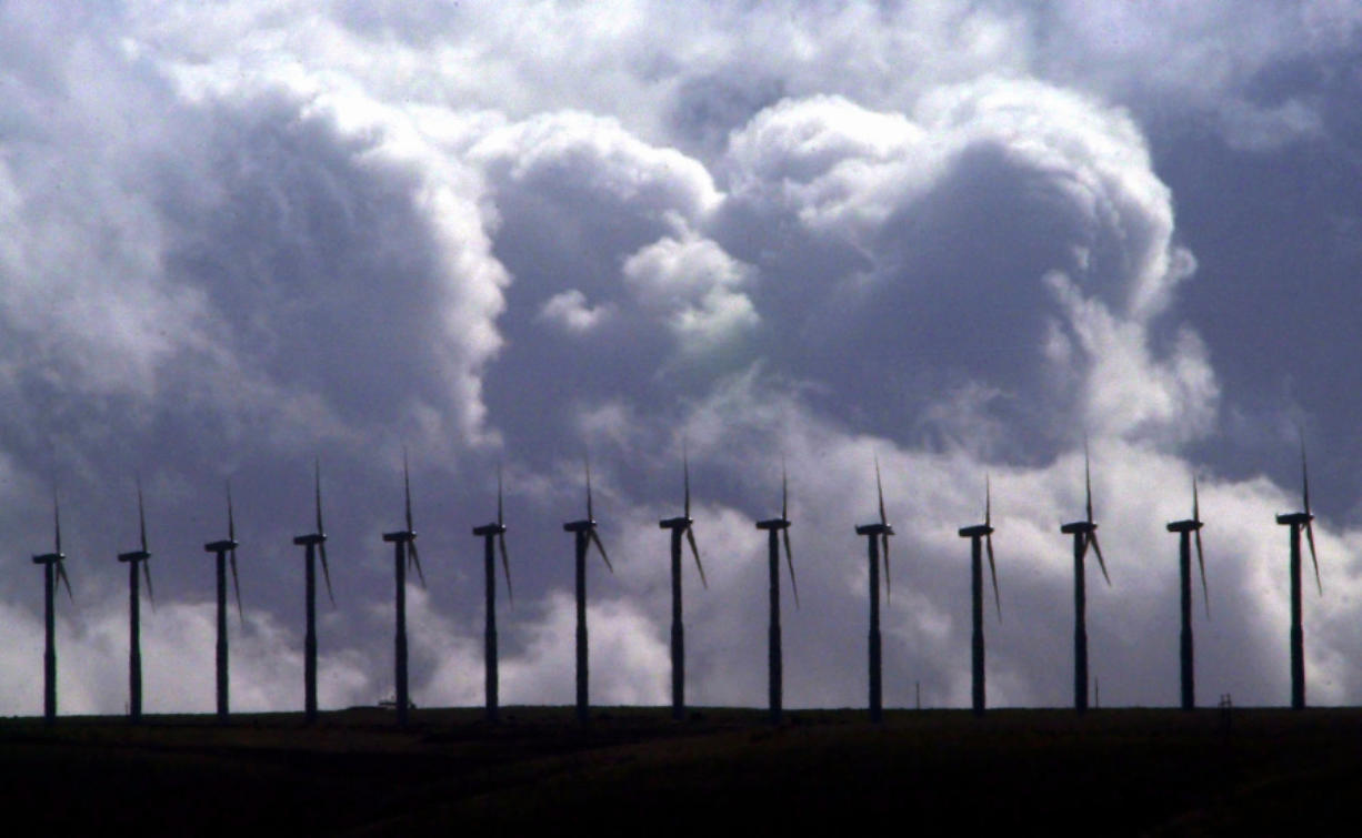 Wind turbines spin under wind-swept, cloudy skies along a ridge line in the Columbia River Gorge near Touchet. (Associated Press files)