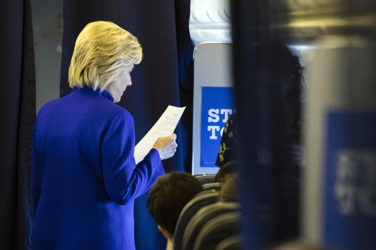 Democratic presidential candidate Hillary Clinton meets with members of her staff onboard her campaign plane en route to Westchester County Airport in White Plains, N.Y., from Florida on Wednesday.