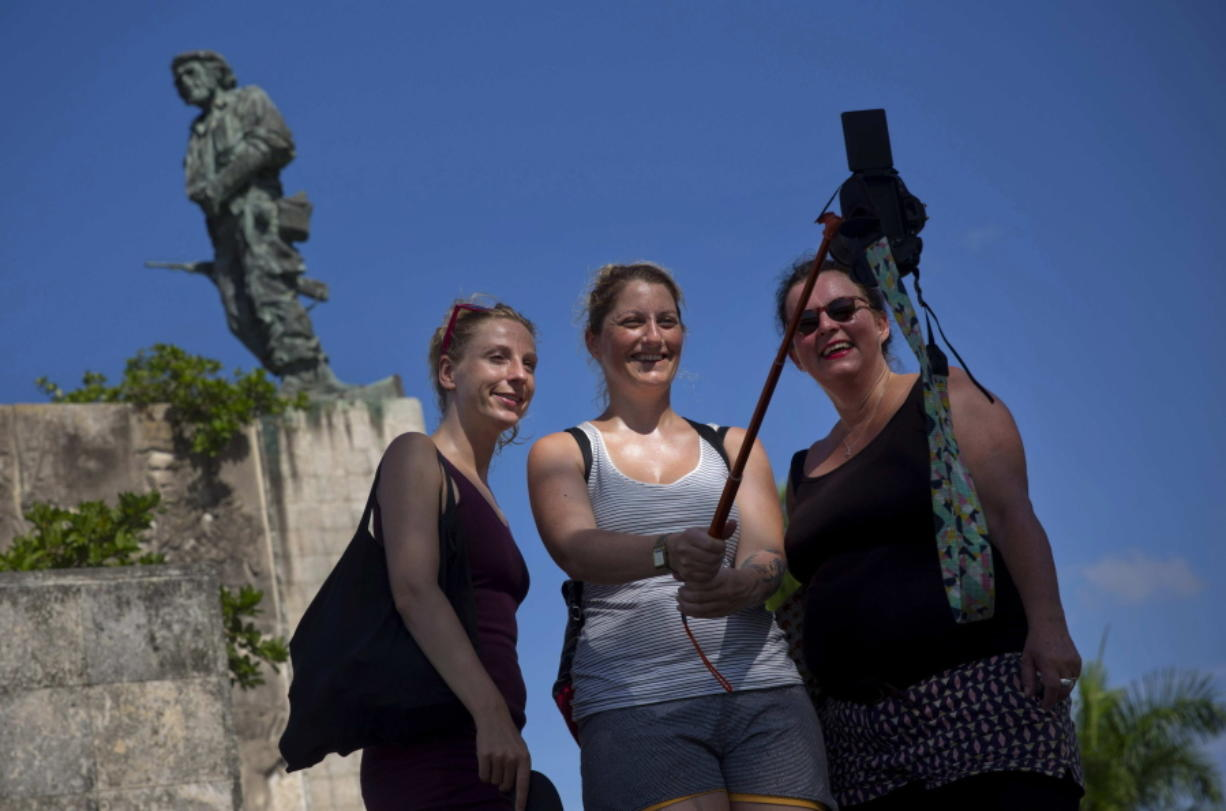 """In this Sept. 2, 2016 photo, tourists takes a selfie by the statue of revolutionary hero Ernesto """"Che"""" Guevara in Santa Clara, Cuba. For travelers without relatives in Cuba it is about $200 each to fly from Fort Lauderdale to Santa Clara."""