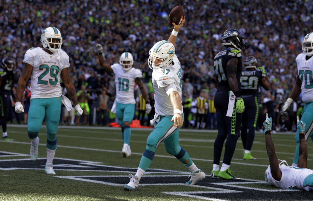 c3513ca70 Miami Dolphins quarterback Ryan Tannehill (17) spikes the ball after  scoring a touchdown against
