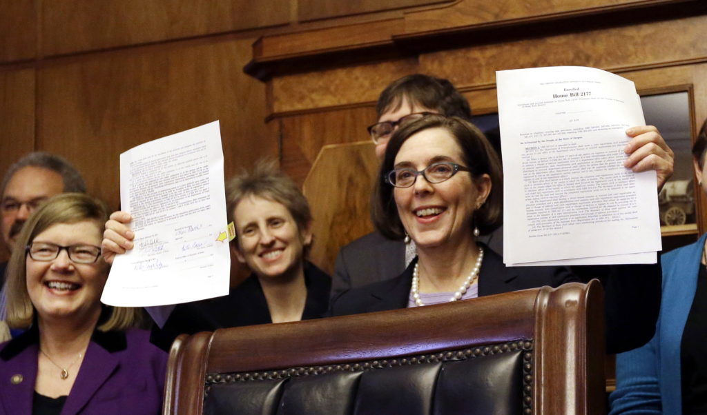 Kate Brown holds up an automatic voter registration bill after signing it March