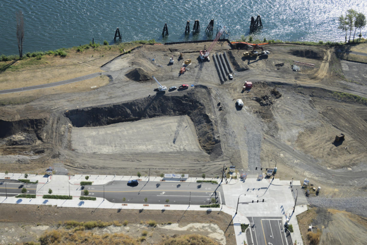 A new public pier at the foot of Grant Street, seen here under early construction in late August, will be a major public attraction at The Waterfront. A hole has been dug for the first building, which can be seen here above Columbia Way. (Ariane Kunze/The Columbian)