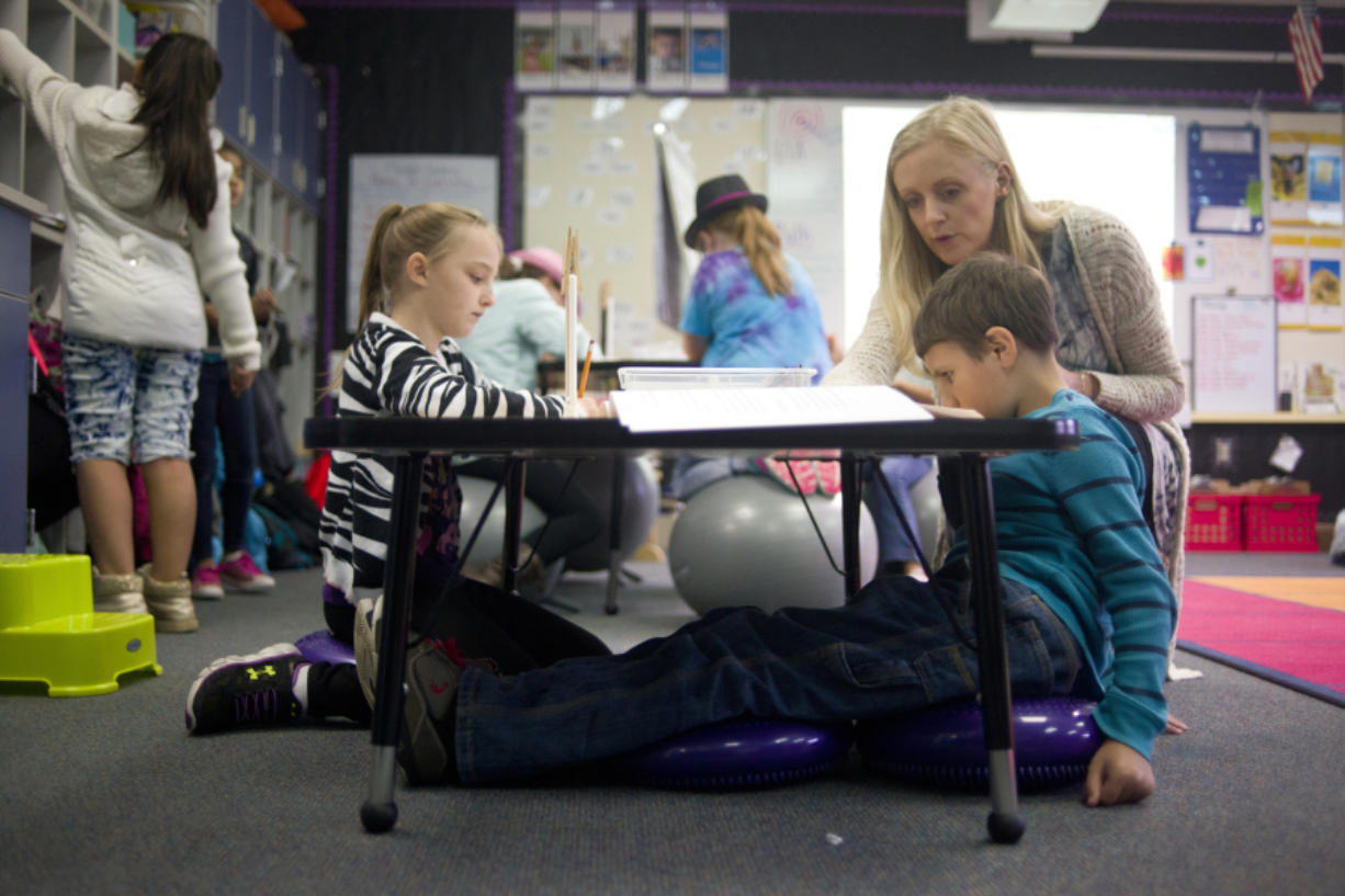 Megan Lascik helps Trevor Maxwell, 8, on an assignment Tuesday while Trevor sits on core discs, one of the multiple flexible seating options in Lascik's third-grade class at Woodland Intermediate School. (Samuel Wilson for the Columbian)
