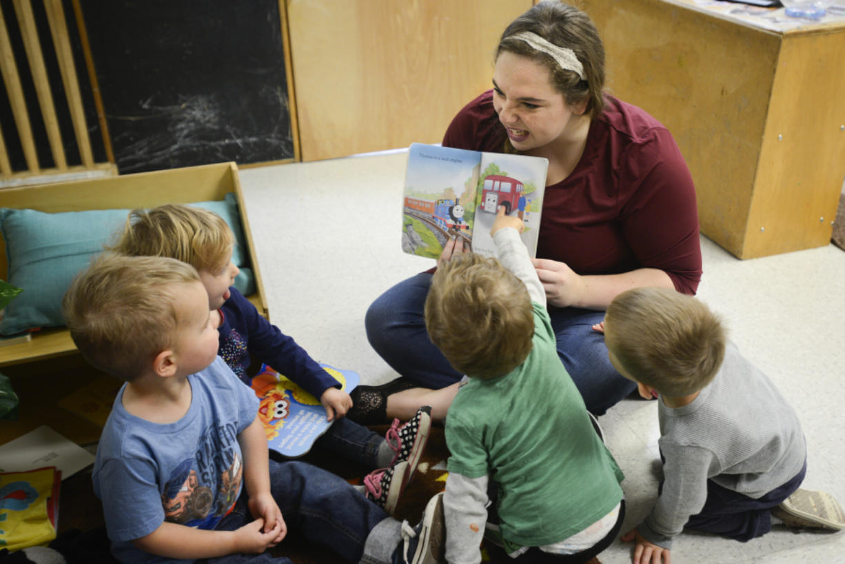 Mariah Laidlaw reads to toddlers Thursday morning at the Central Park Child Care Center in Vancouver. The Central Park center is one of 29 centers making up the Clark County Child Care Consortium.