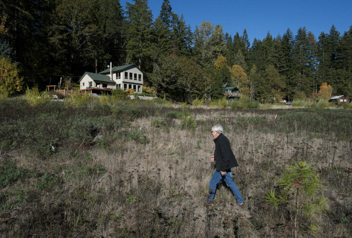 Al Greenwood walks through what used to be the bottom of Northwestern Lake along the White Salmon River. Five years after the breach, cabin owners are still adjusting to life without the lake.