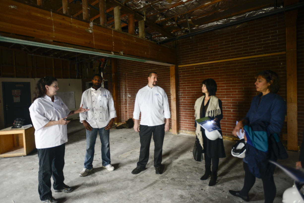 Clark College Cuisine Instructor Aaron Guerra, center, talks Thursday to interested wine and beer distributors about Clark College's new culinary program during a tour of the facility that's under construction, aiming to open next fall.