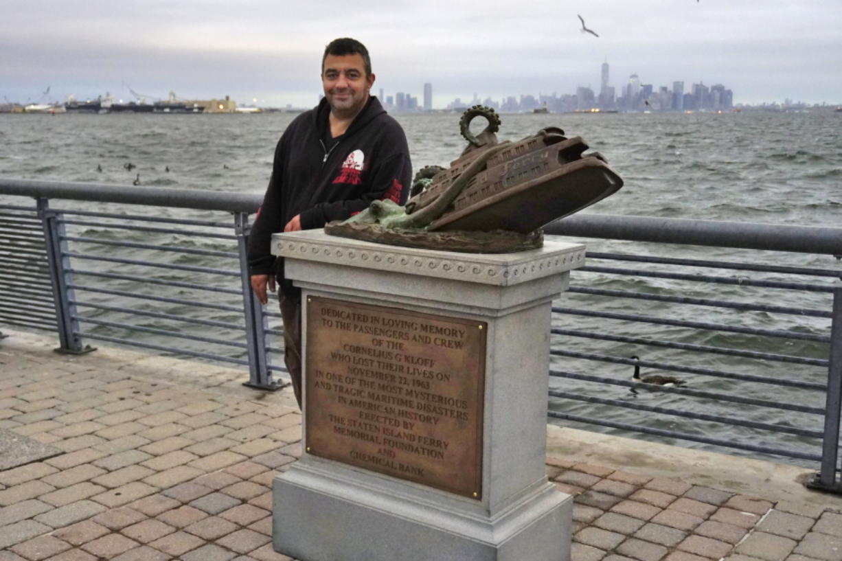 Artist Joseph Reginella poses for a photo, in the Staten Island borough of New York, with the cast bronze faux monument dedicated to the memory of the victims of the steam ferry Cornelius G. Kolff.