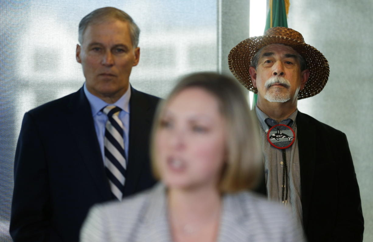 Gov. Jay Inslee, left, and Mel Sheldon Jr., chairman of the Tulalip Tribe, listen to Christy Goldfuss, managing director of the White House Council on Environmental Quality, speak Tuesday at a press conference in Seattle. (Ted S.