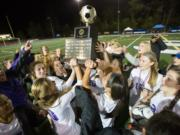 Columbia River players lift the Class 2A state championship trophy after they defeated Liberty in a shootout on Saturday, Nov. 19, 2016 at Shoreline Stadium in Shoreline, Wash.