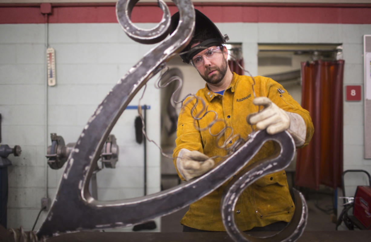 Scott Patzer works on a metal lamp at Clark College's metal sculpting class in Vancouver on Nov. 14. Patzer is an artist pursuing a degree in welding. (Natalie Behring for the Columbian)