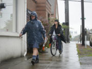 Mary Siebert, left, delivers mail to the Clark County Veterans Assistance Center in Vancouver in the rain on Oct. 13.