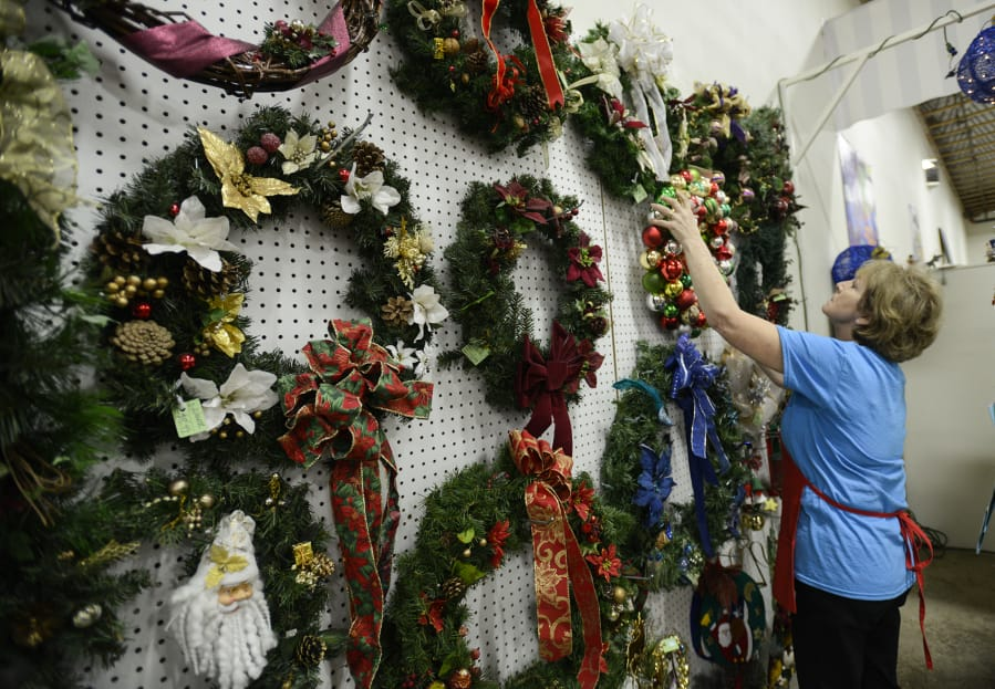 volunteers sift through thousands of secondhand holiday items to be sold at a christmas tail - A Christmas Tail