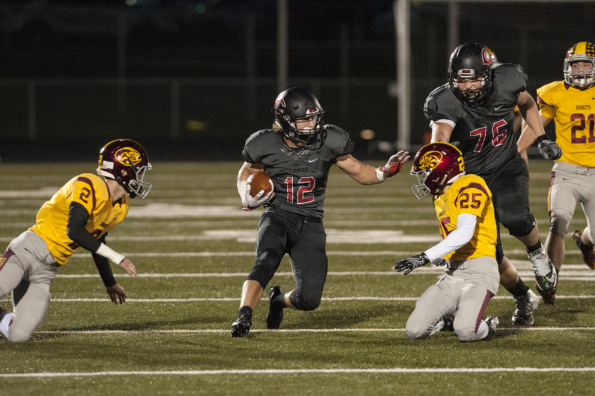 Camas' running back Michael Matthews (12) escapes Enumclaw's defense during the first quarter. He rushed for 35 yards and one touchdown.