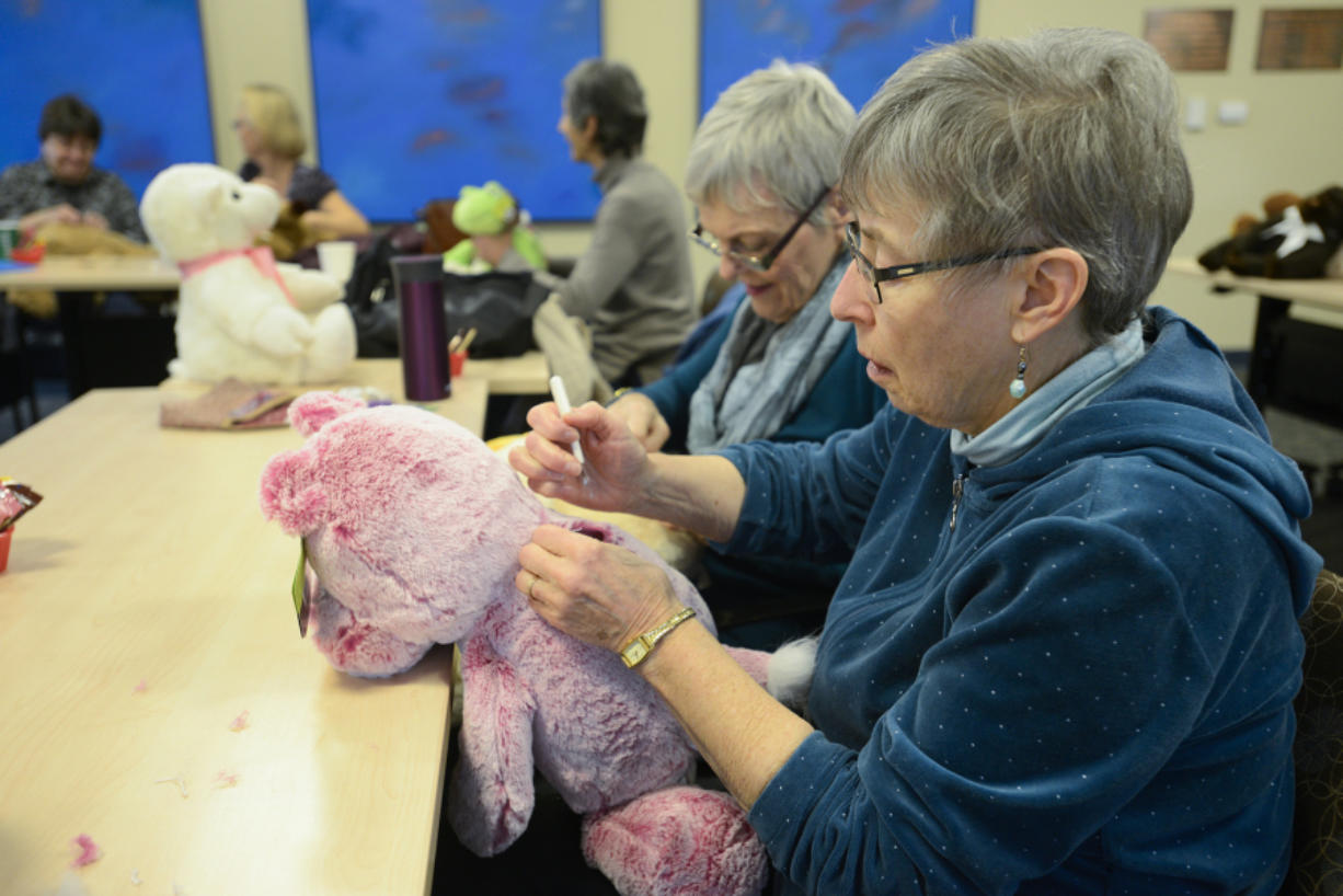 Donna Shaver tears the seam on a stuffed teddy bear in order to insert a small bag of rocks. Volunteers from the Unitarian Universalist Church of Vancouver created weighted stuffed animals for clients at the Children's Center.