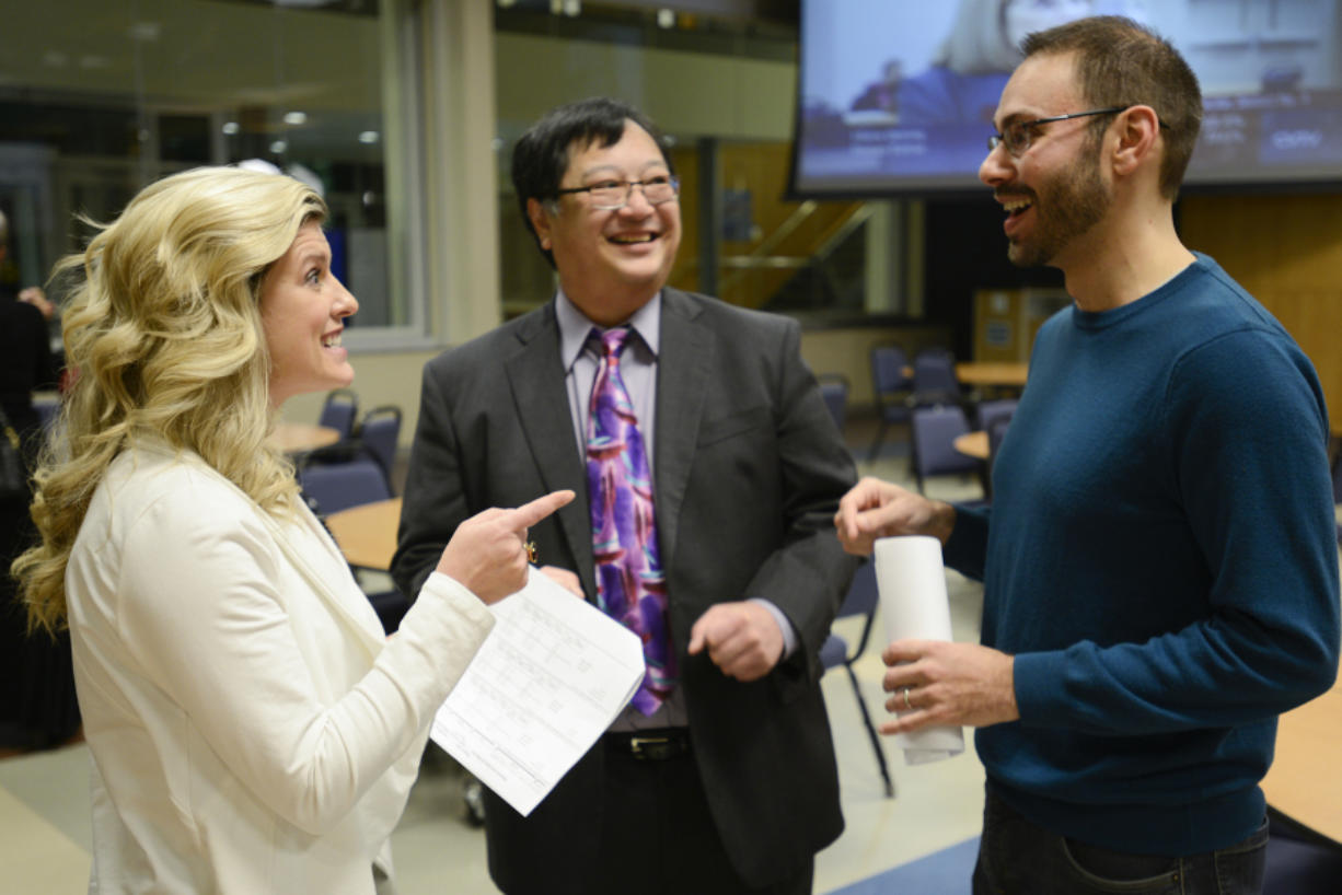 Katie Archer, campaign manager for Bring Vancouver Home, left, speaks to Andy Silver, executive director of the Council for the Homeless, right, and Gary Akizuki, treasurer for Bring Vancouver Home, Tuesday after learning preliminary results of Proposition 1.