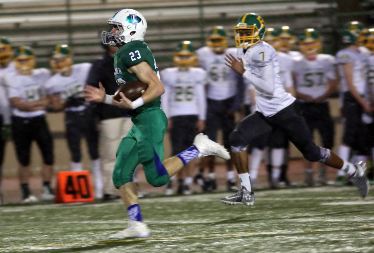 Glen Perry Jr. (23) of Mountain View, runs with the ball as he is pursued by Bishop Blanchet's Jamiek Satterwhite. Perry had 174 yards rushing and three TDs Saturday.