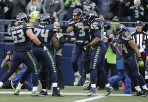 fdac5e66797 Seattle Seahawks quarterback Russell Wilson (3) is greeted by teammates  after Wilson caught a