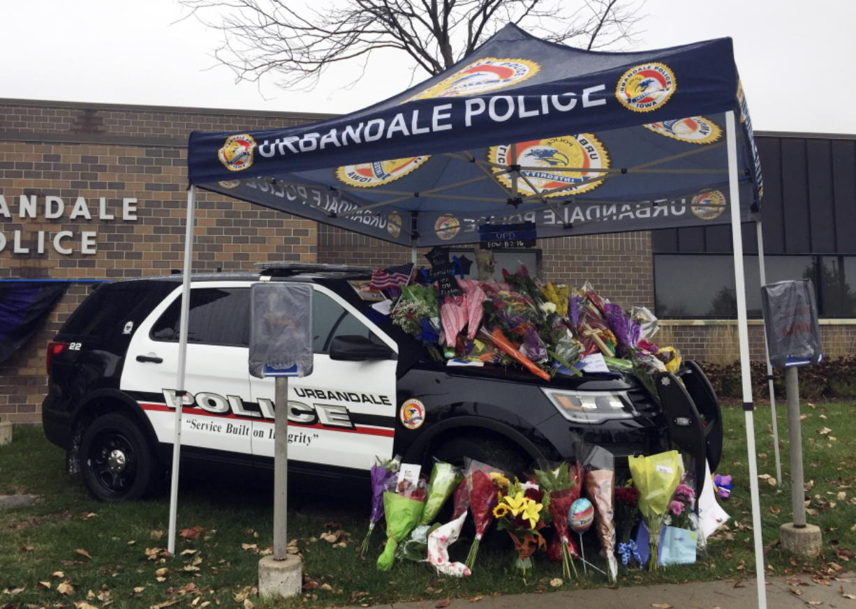 Items are left at a memorial outside the police department in Urbandale, Iowa, for two police officers shot to death Wednesday morning.