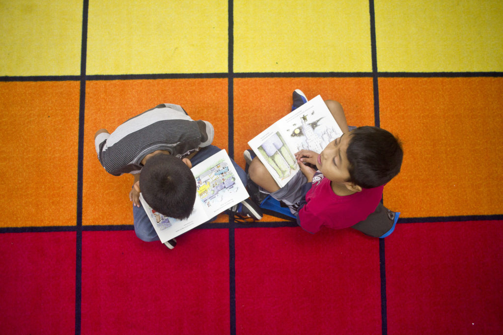 """Alexander Lorenzo, left, 9, reads """"The Gym Teacher from the Black Lagoon"""" to Christopher Lopez, 9, in Jennifer Crosby's third grade class at Woodland Intermediate School on Tuesday, October 25, 2016. Crosby and fellow third grade teacher, Megan Lascik, are giving students flexible seating options in class to help them learn more comfortably. (Samuel Wilson for the Columbian)"""