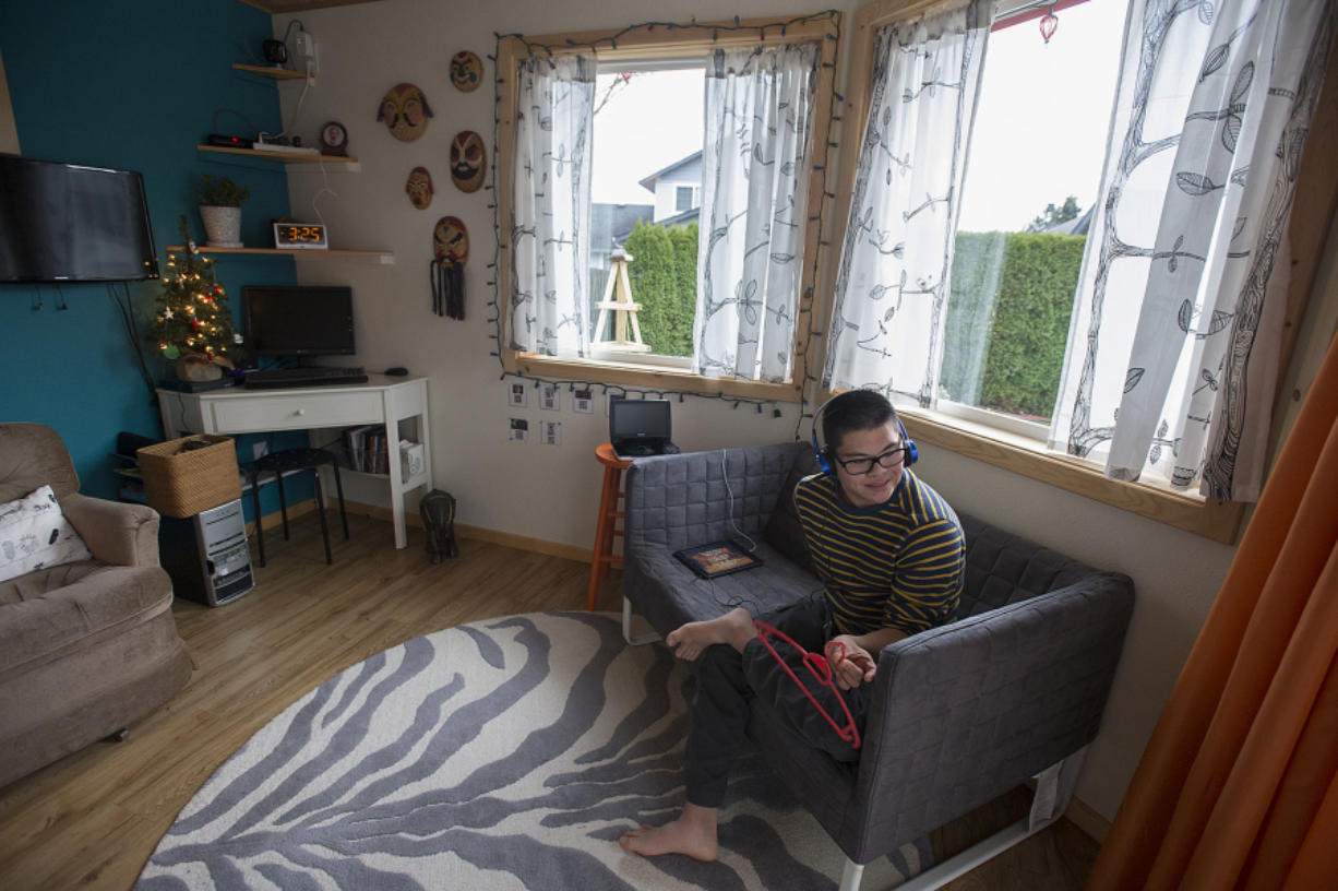 Yung Ting Engelbrecht enjoys a show on his tablet while relaxing at his east Vancouver home, an accessory dwelling unit that's attached to his parents' house.