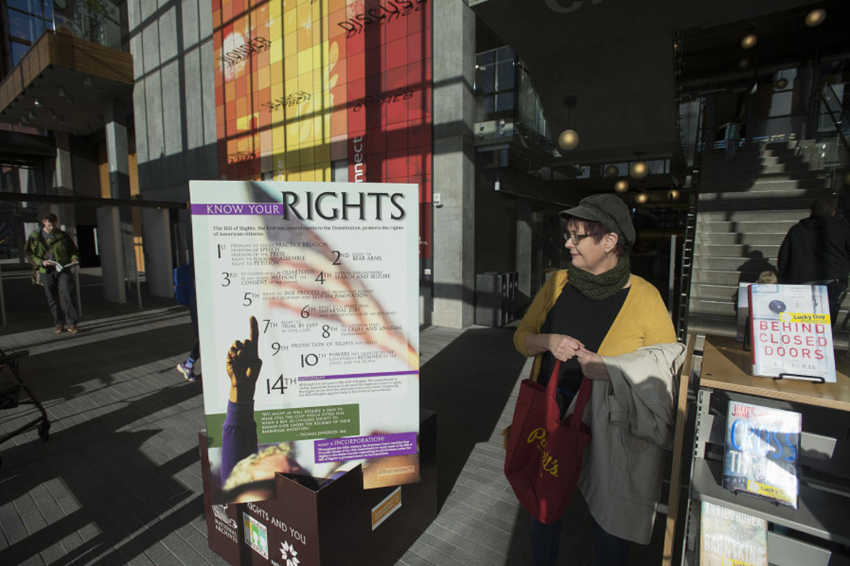 Vancouver resident Carmen Weninger looks over the Bill of Rights display at the Vancouver Community Library on Tuesday morning. (Amanda Cowan/The Columbian)